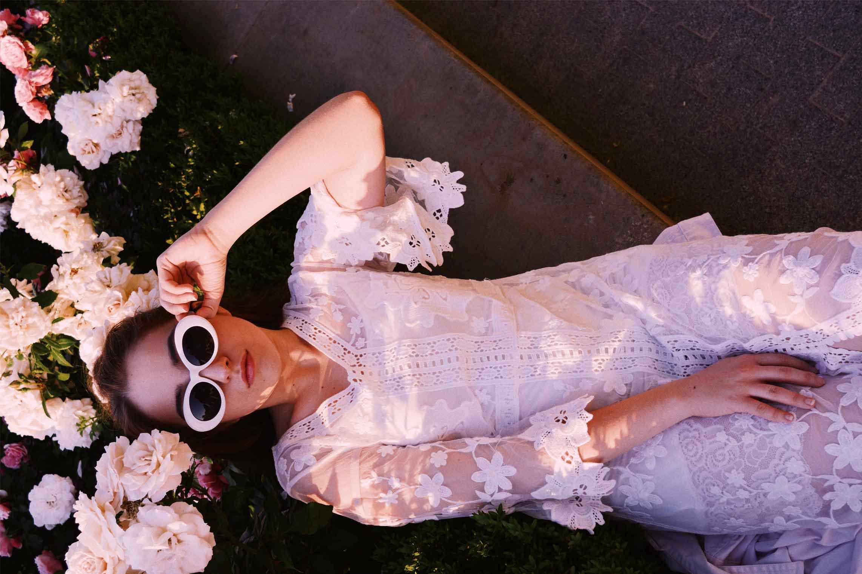 Imagen para estrategia de marketing digital de mujer posando con un vestido blanco y gafas de sol.